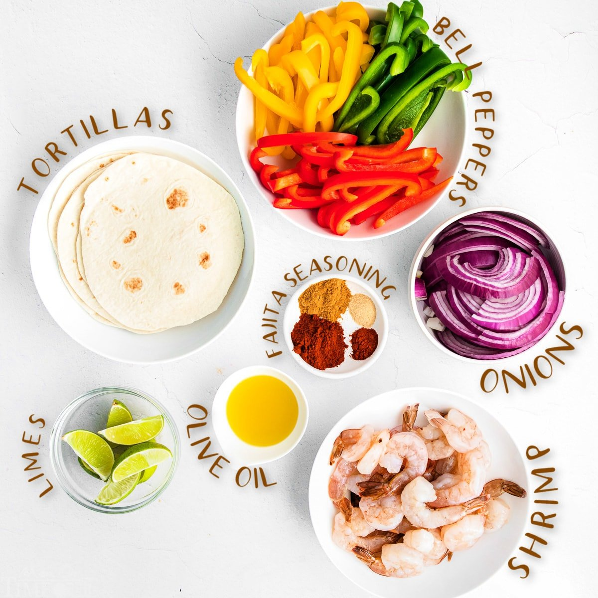 fajita ingredients all measured out in small bowls on white surface.