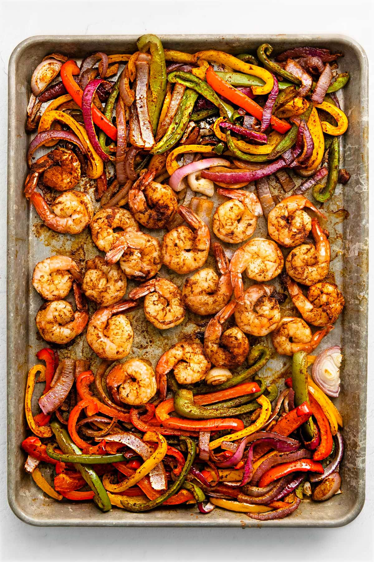 shrimp fajitas on a sheet pan with shrimp in the center and veggies on the sides.
