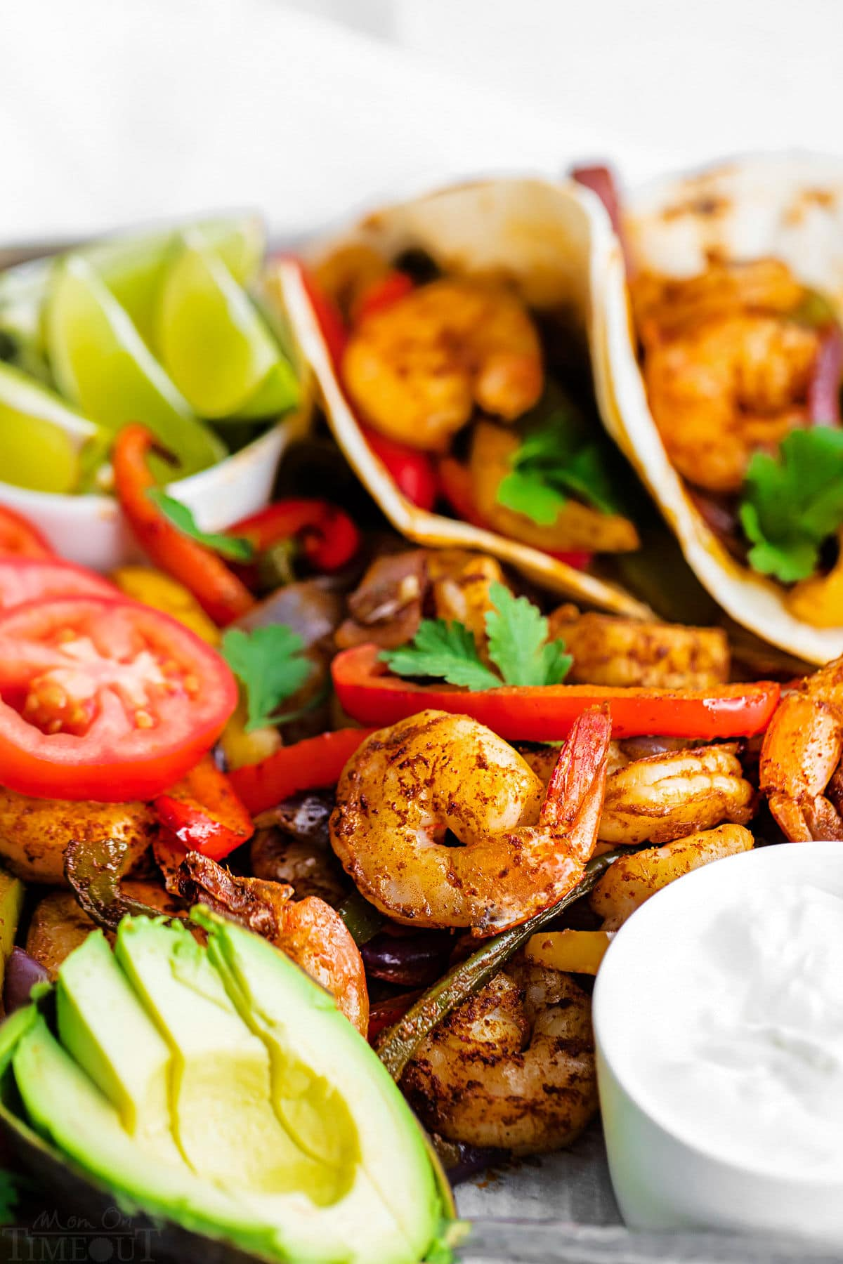 close up look at the shrimp fajitas on sheet pan with sliced avocado and sour cream.