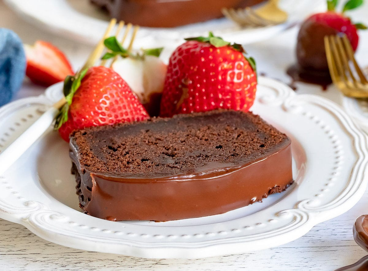 slice of chocolate pound cake on white plate with strawberries