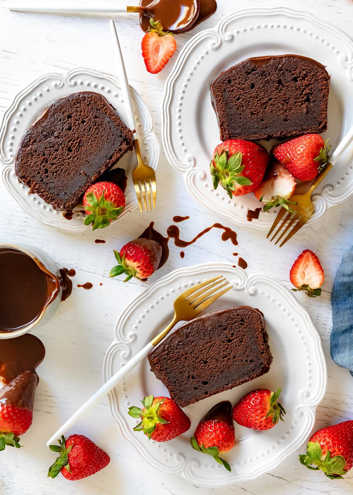 top down view of three slices of pound cake on white plates with strawberries scattered about and white and gold forks on plates