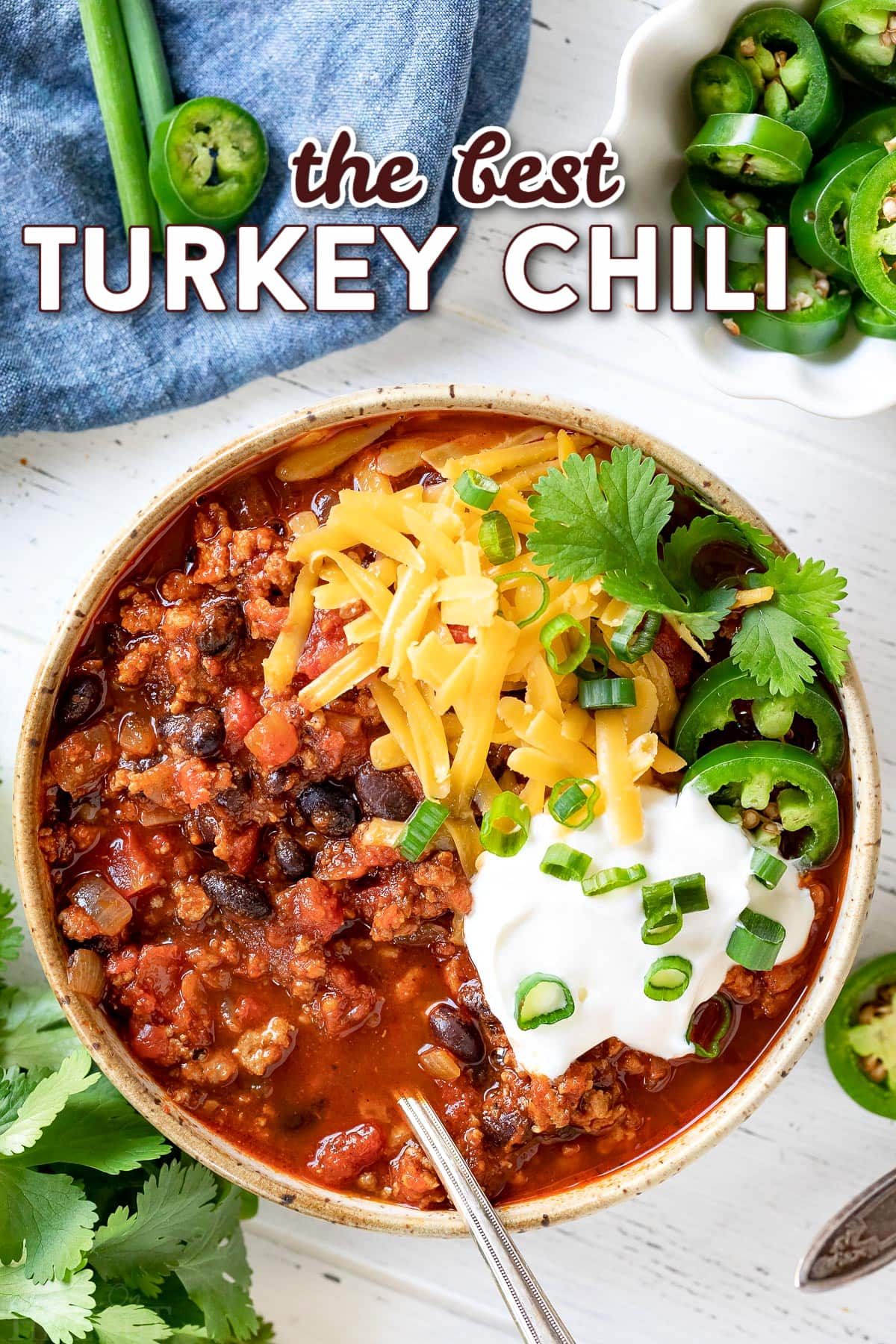 bowl of turkey chili with cheese sour cream and cilantro on top with title overlay.