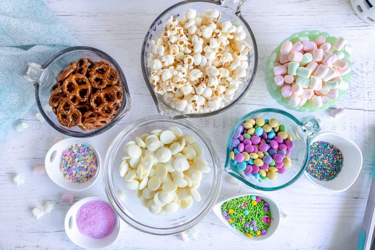 snack mix ingredients measured out into small bowls.