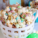 easter snack mix in white basket with pretzels, marshmallows and popcorn.
