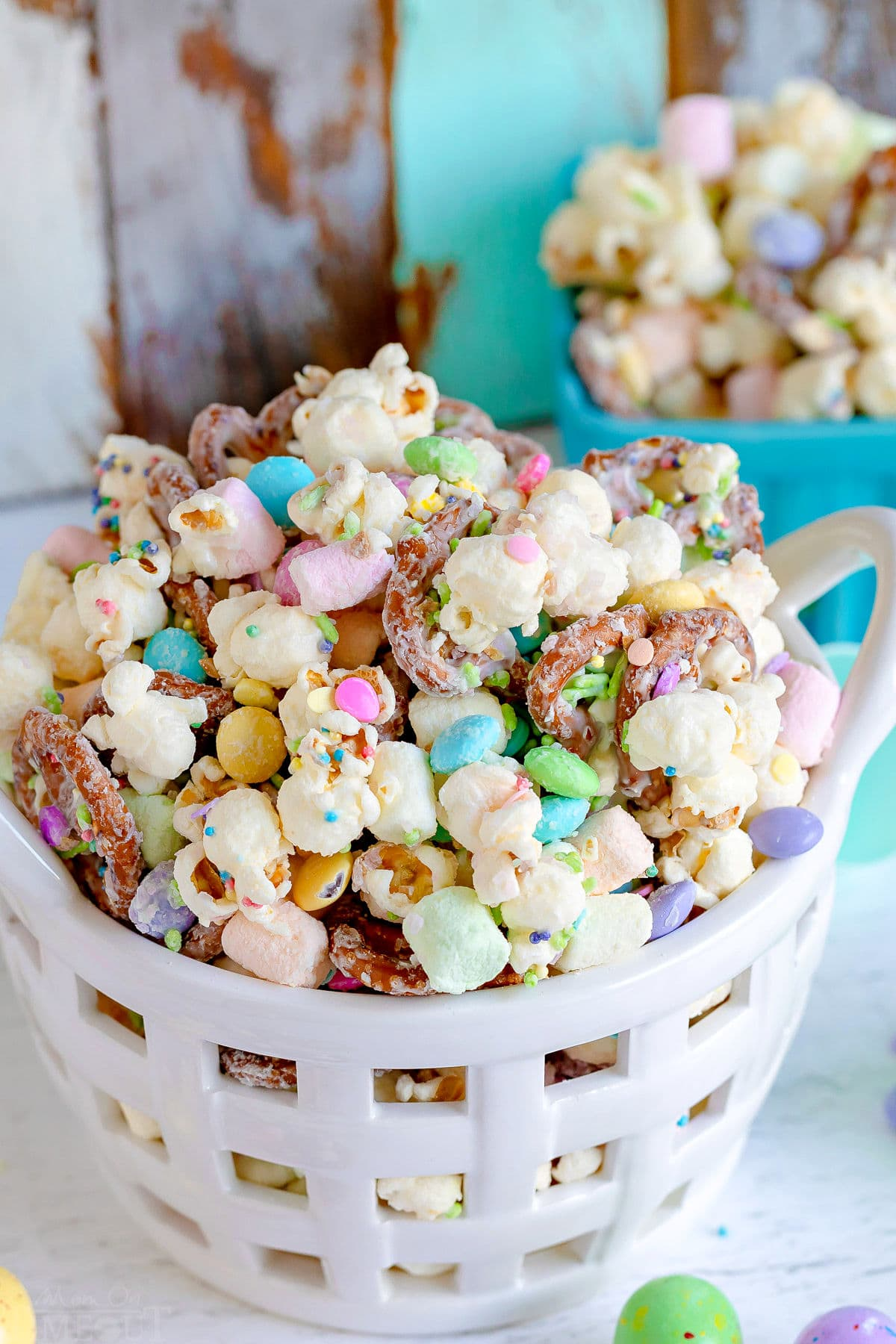 bunny bait snack mix with popcorn and pretzels in a white ceramic basket.