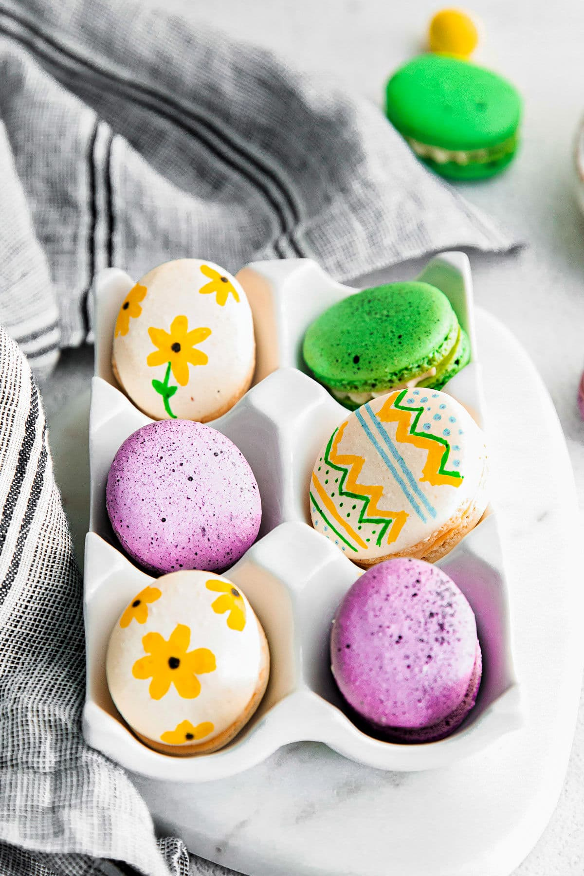 6 macarons decorated like eater eggs in white ceramic egg crate.