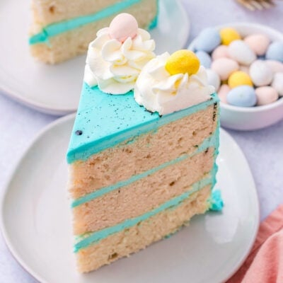 a slice of easter cake with bright blue frosting decorated with cadbury eggs.