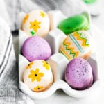 french macarons decorated as easter eggs sitting in white egg crate.