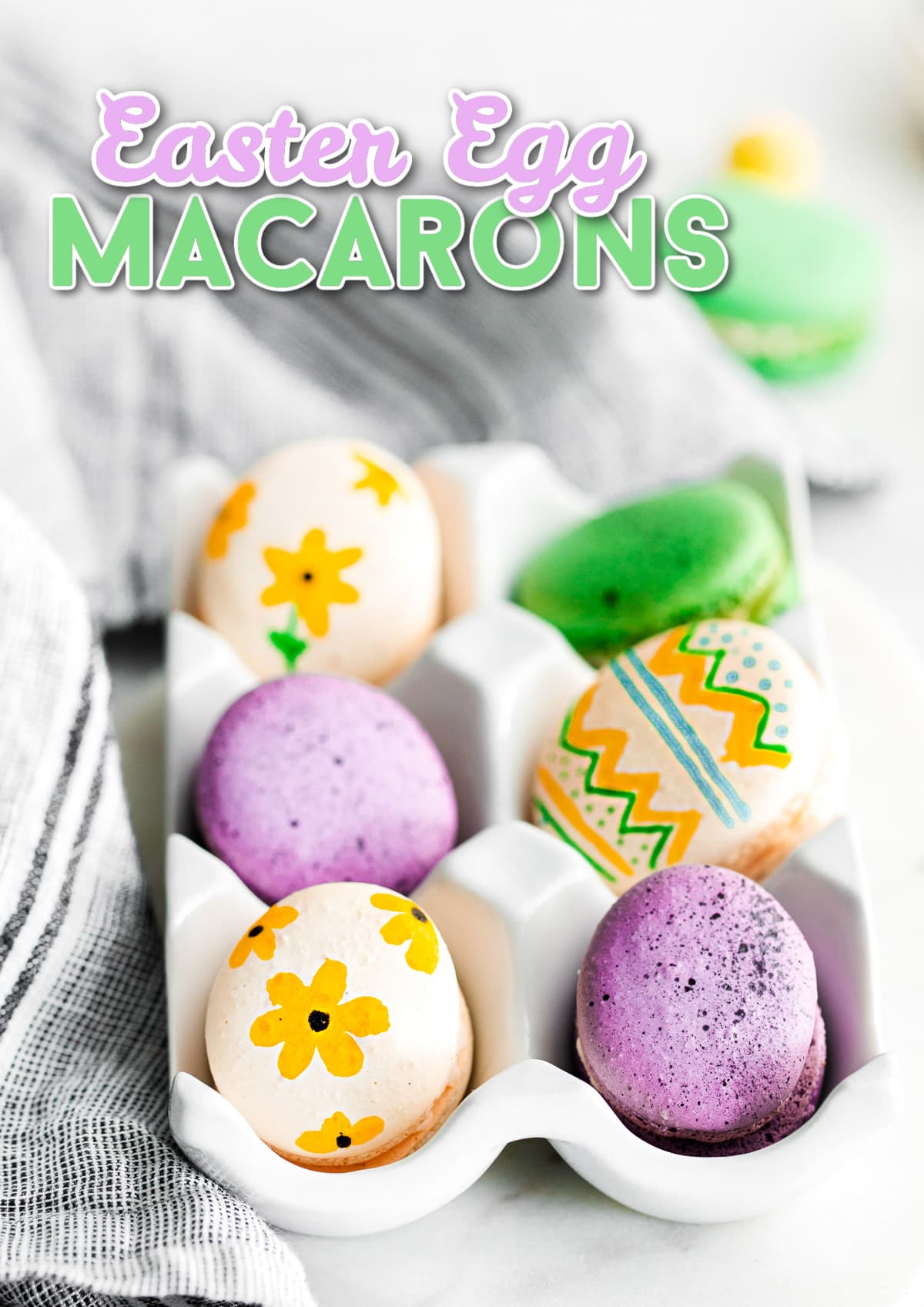 french macarons decorated as easter eggs sitting in white egg crate with title overlay at top of image.