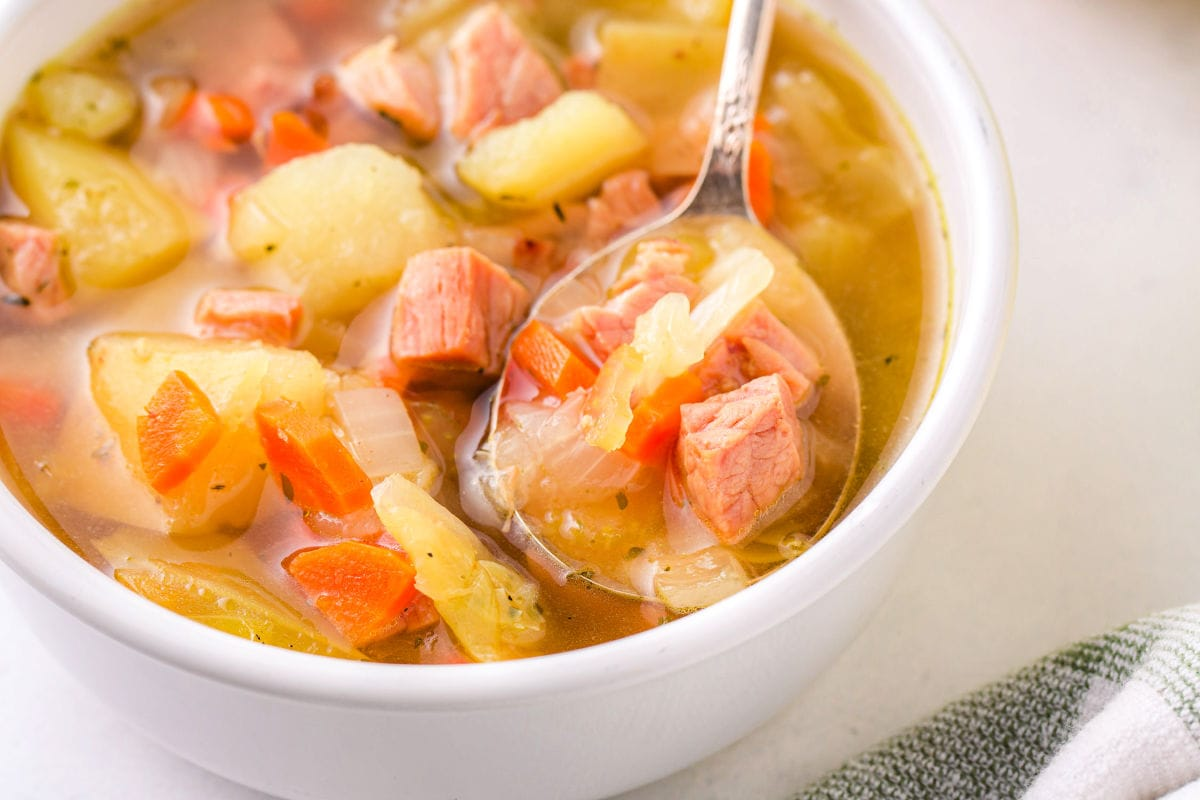 spoon in bowl filled with cabbage and ham soup.