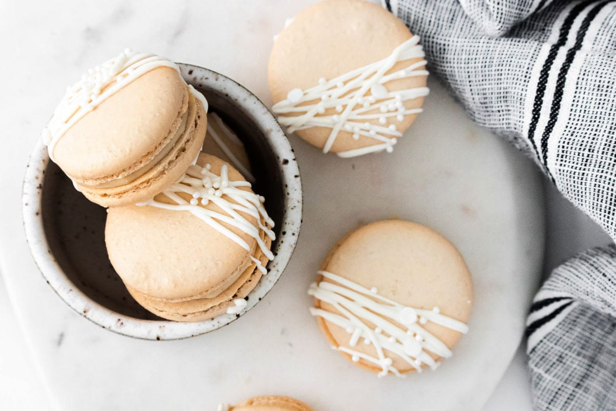 top down look at macarons decorated with white chocolate.