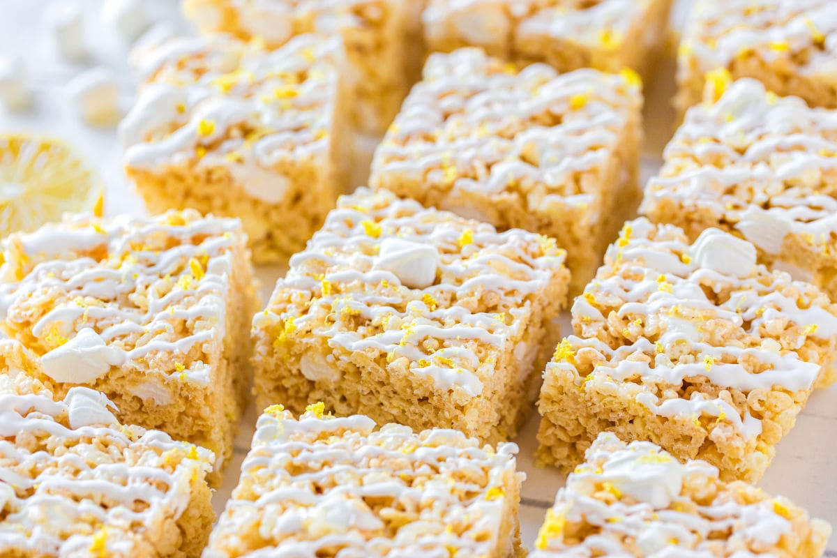 rice krispie treats cut into squares on white surface with white drizzle on top of treats.