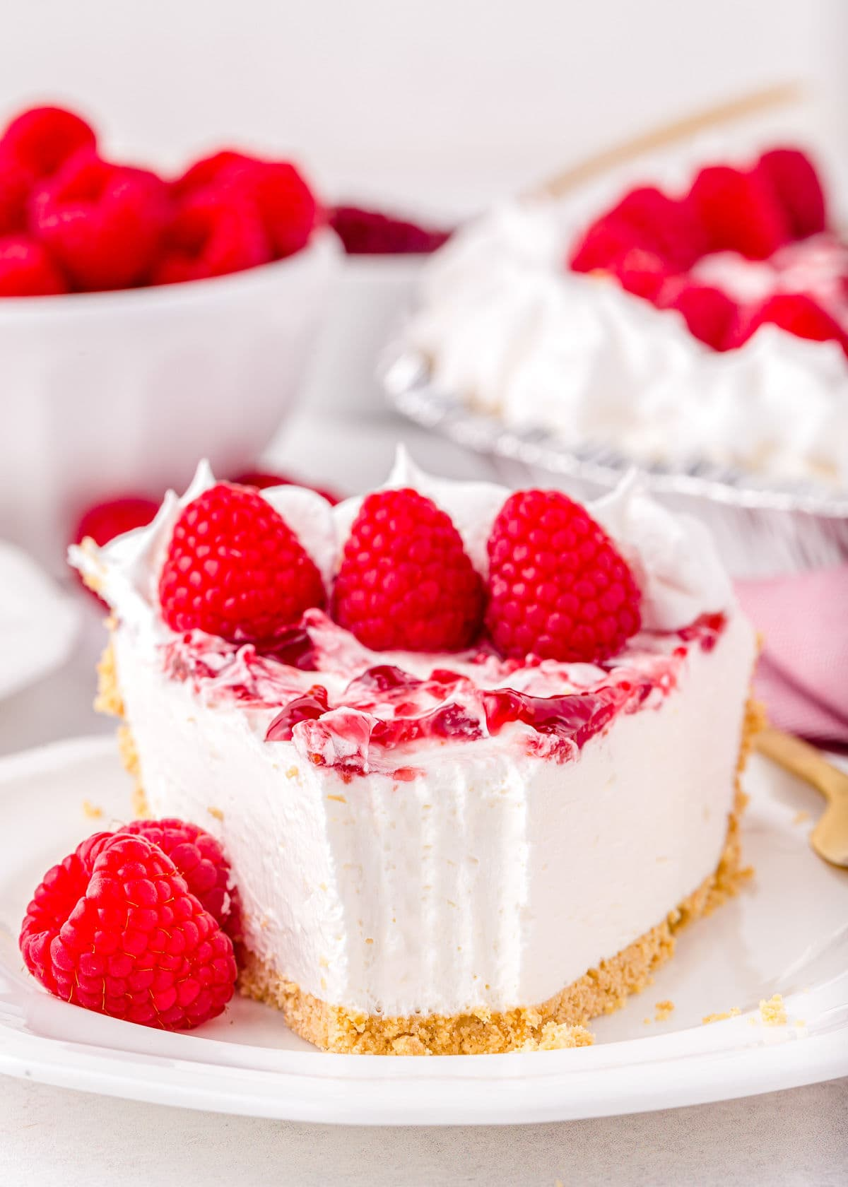 piece of raspberry no bake cheesecake with bite taken sitting on white plate and garnished with fresh raspberries.