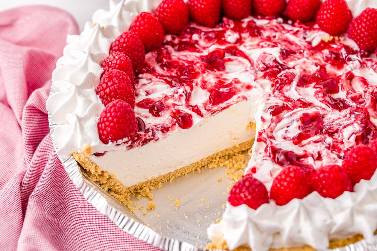 whole raspberry cheesecake with just 1 slice removed sitting next to pink towel.