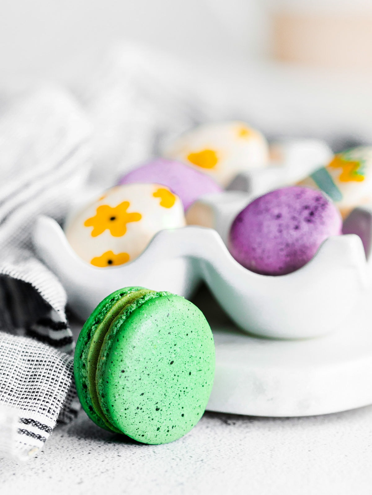 green speckled macaron sitting in front of egg tray.
