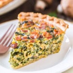 piece of spinach quiche on white plate.
