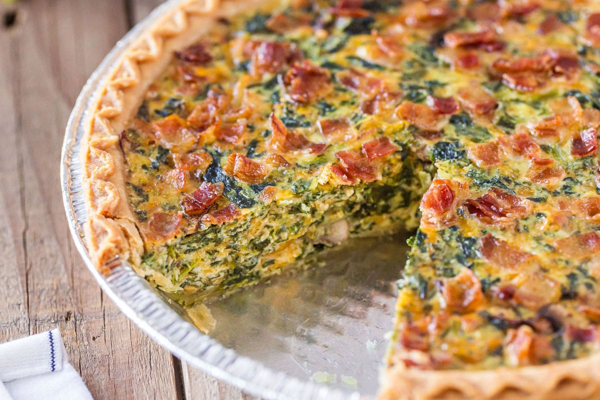spinach quiche recipe with piece removed.