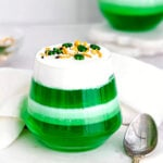 layered green and white jello cups on marble surface.