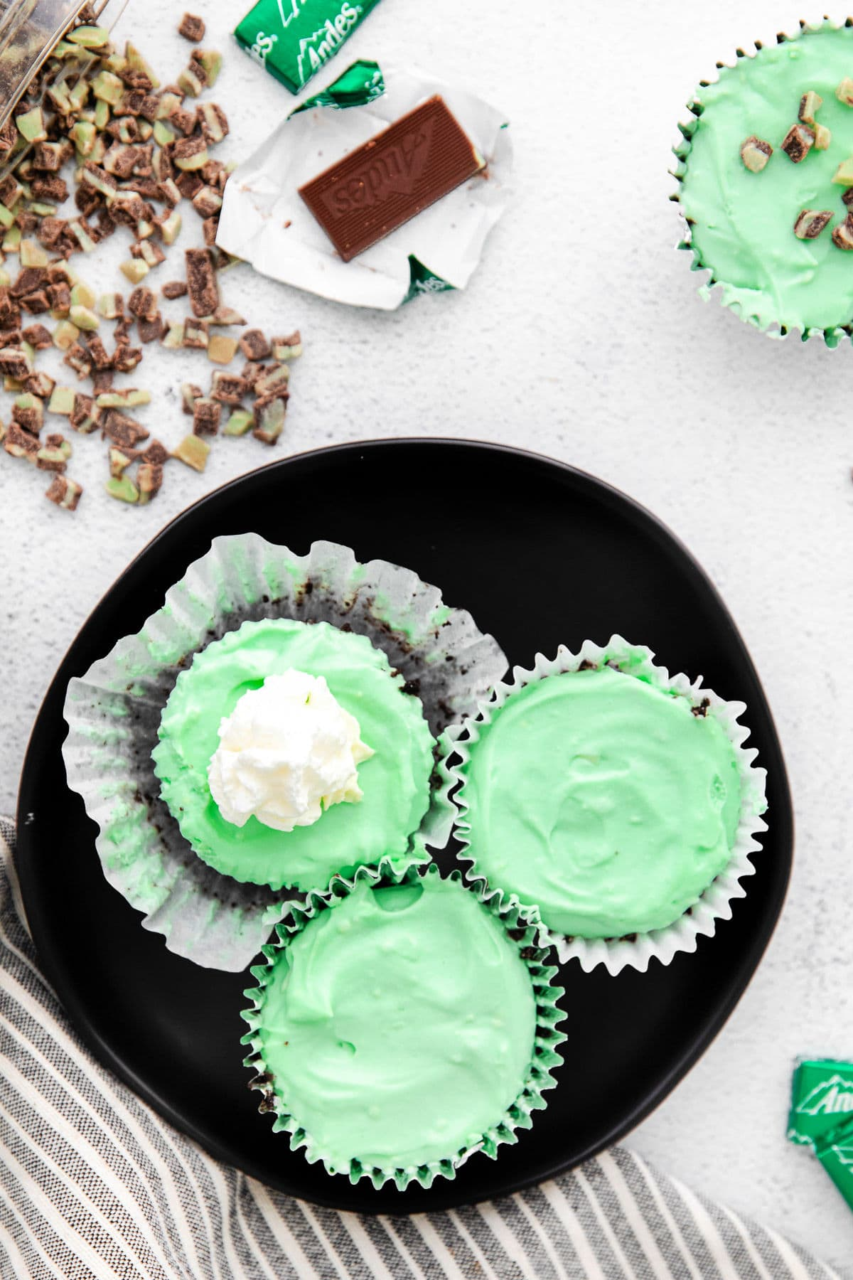 top down look at green mini cheesecakes on a black plate one topped with whipped cream.