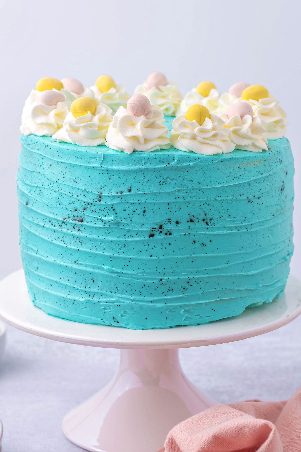 whole easter cake decorated with turquoise frosting and cadbury eggs.