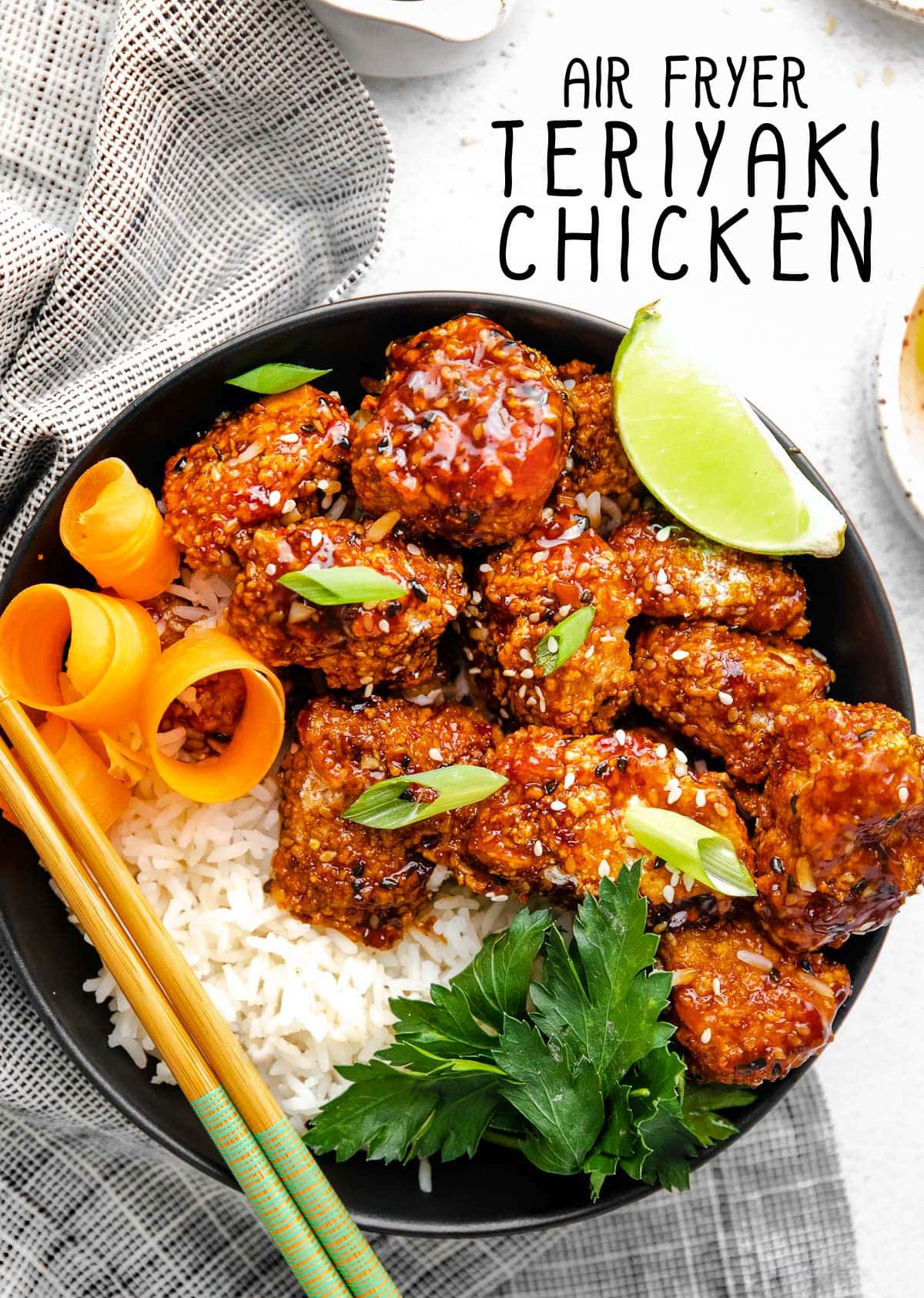 teriyaki chicken with rice in a black bowl next to a striped black and white towel. title overlay at top of image.