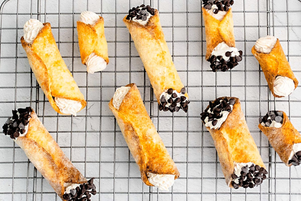 filled cannolis on metal rack ready to eat.