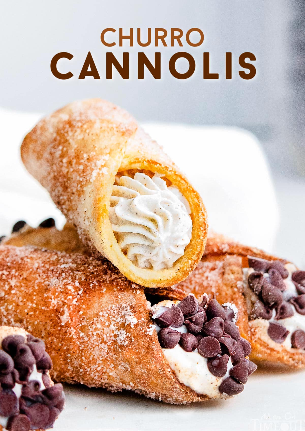 three cannolis sitting on white plate with cannoli filling and chocolate chips.
