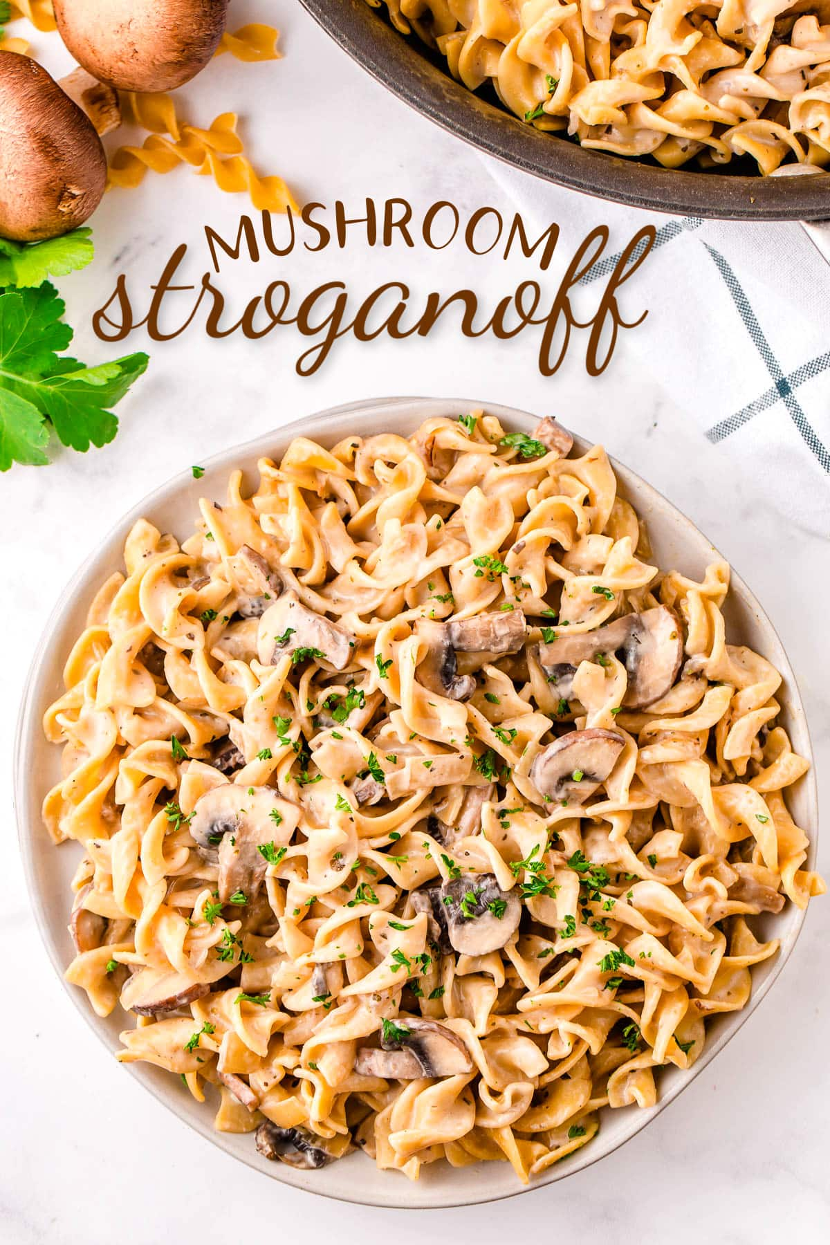 top down view of mushroom stroganoff piled high on round white plate garnished with parsley. text overlay at top of image.