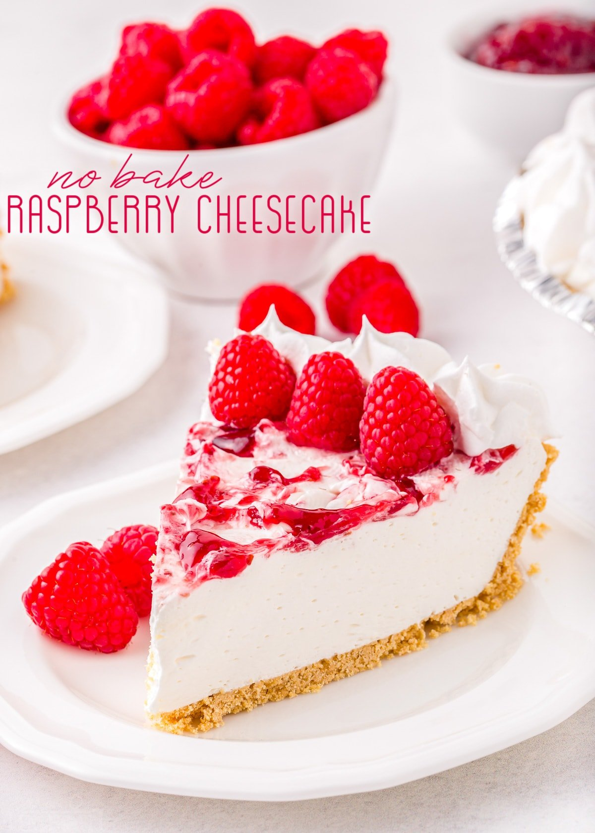 piece of cheesecake on plate garnished with fresh raspberries with title overlay.