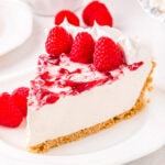 piece of cheesecake on plate garnished with fresh raspberries.