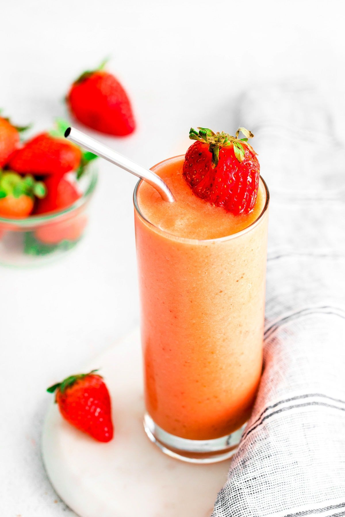 strawberry smoothie with mango in a tall glass on white surface.