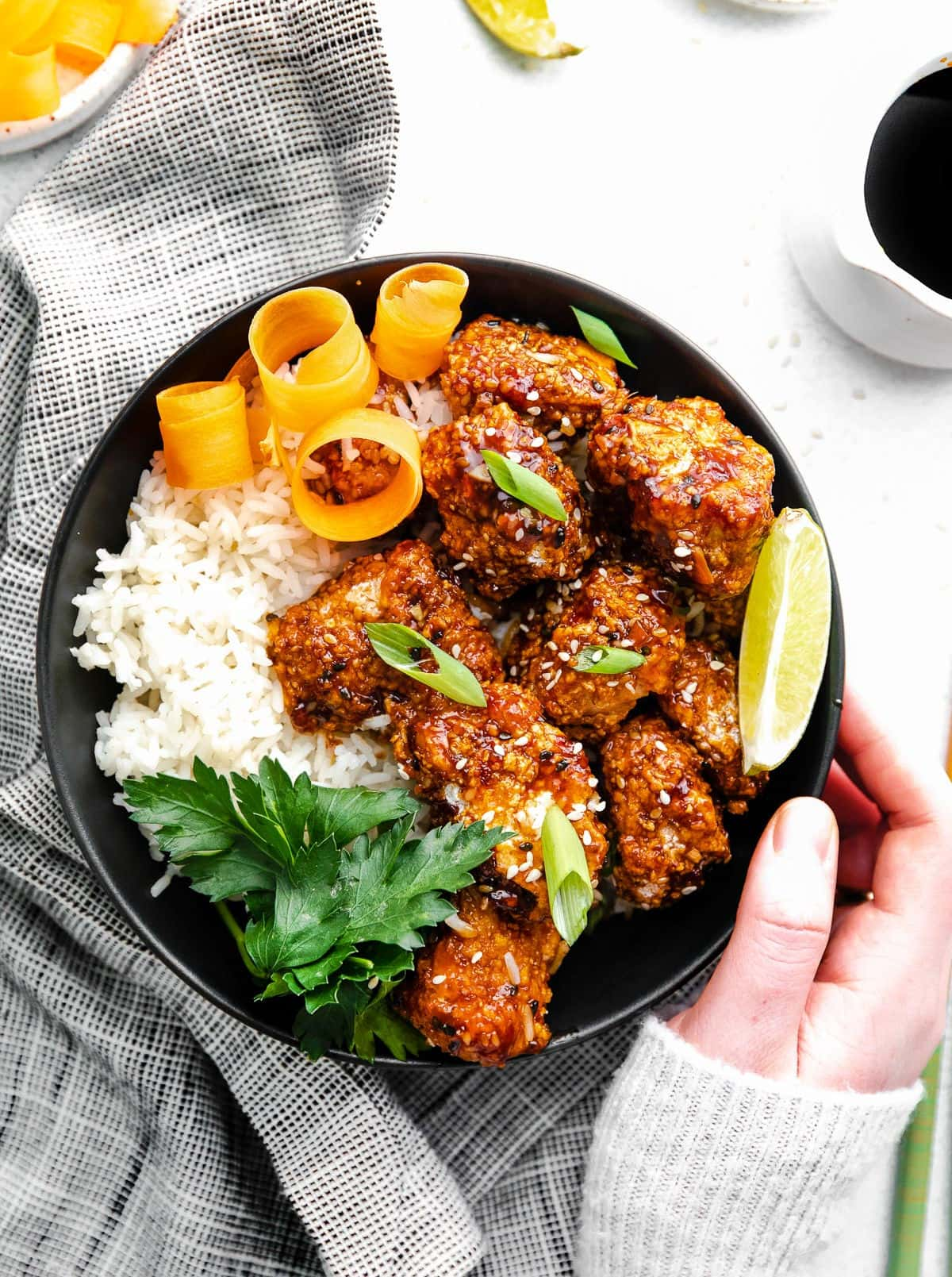 black bowl with rice and teriyaki chicken garnished with orange peels, lime wedge and parsley.
