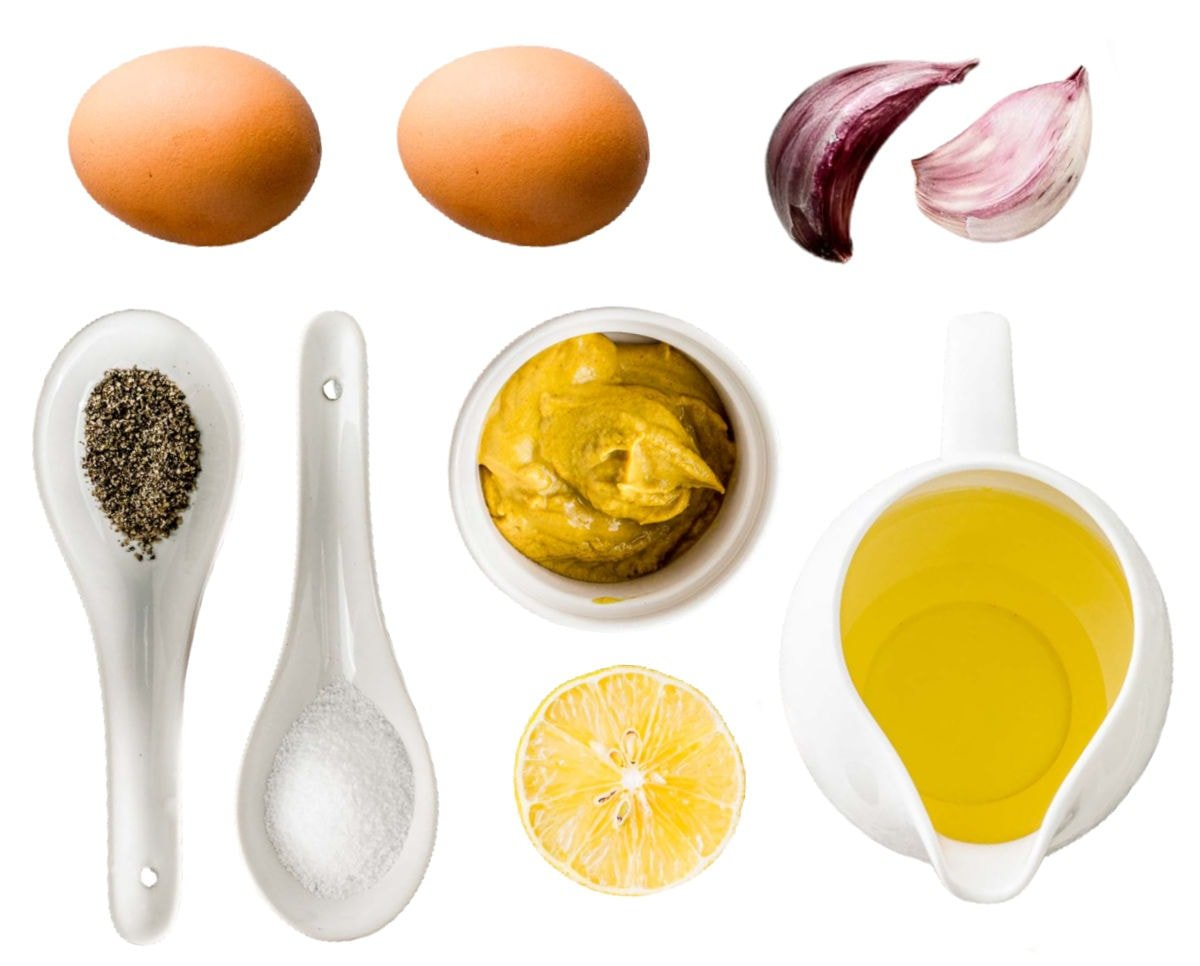 aioli ingredients measured out in small bowls on white background.