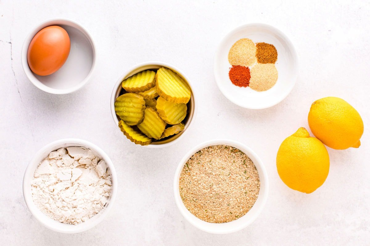 air fryer pickles ingredients measured out in small bowls on white surface.