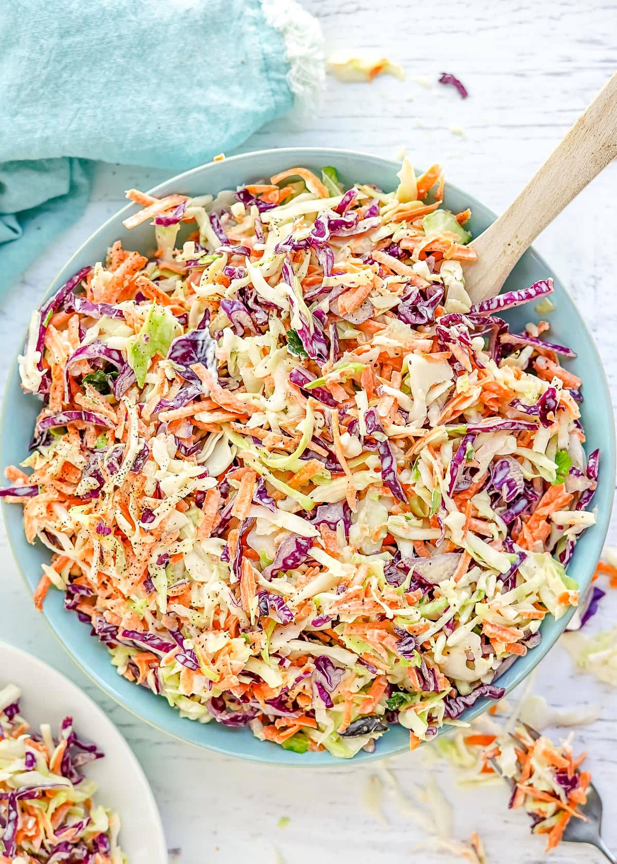 coleslaw prepared in a light blue bowl with wood spoon in the bowl.