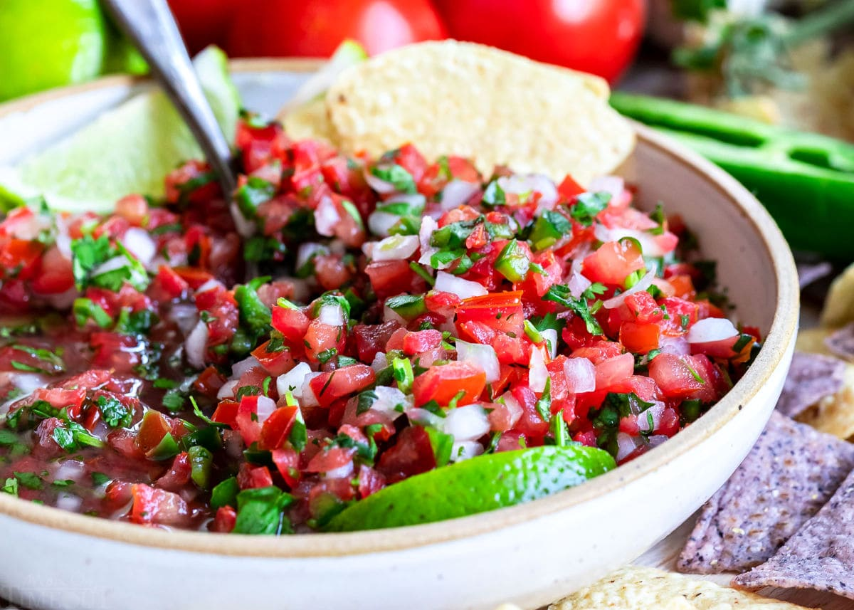 close up look at pico de gallo all mixed up in a medium sized clay bowl with chips around it.