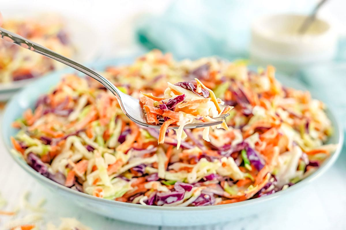 forkful of coleslaw held in front of large bowl with coleslaw in it.