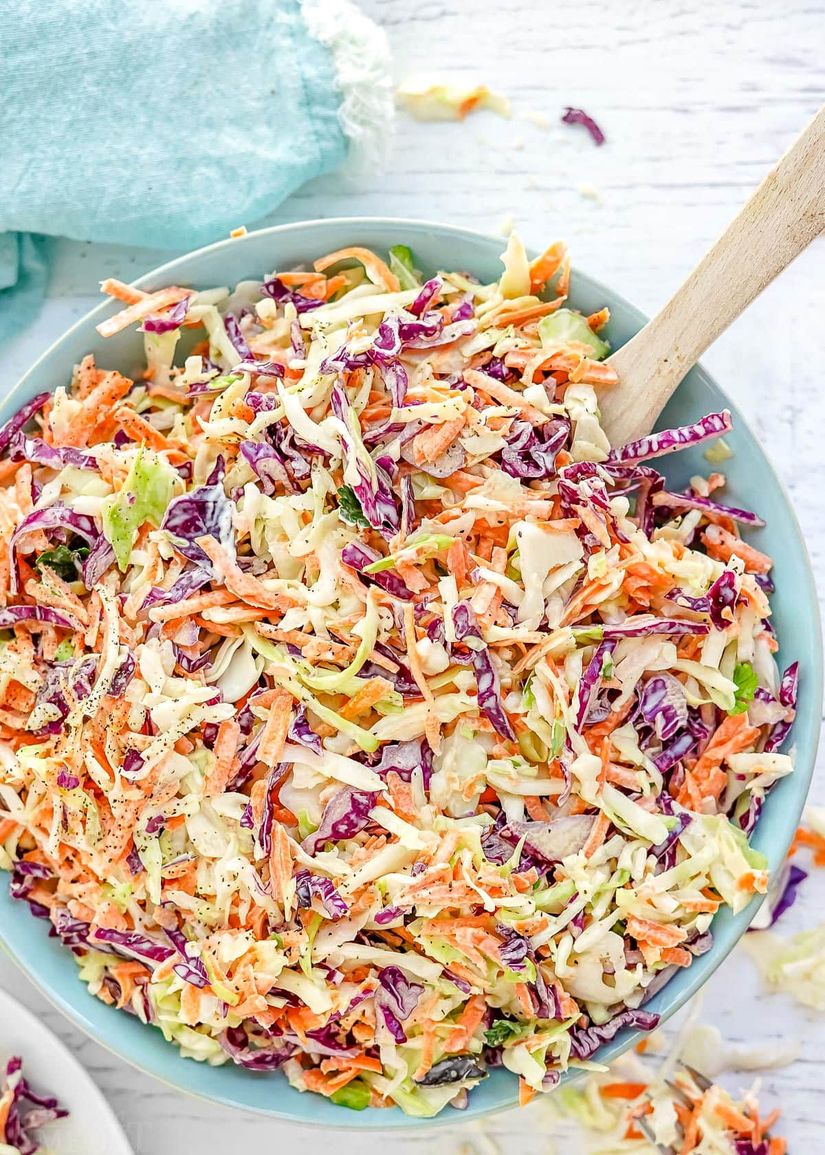 close up look at tri colored coleslaw in light blue bowl ready to be served.