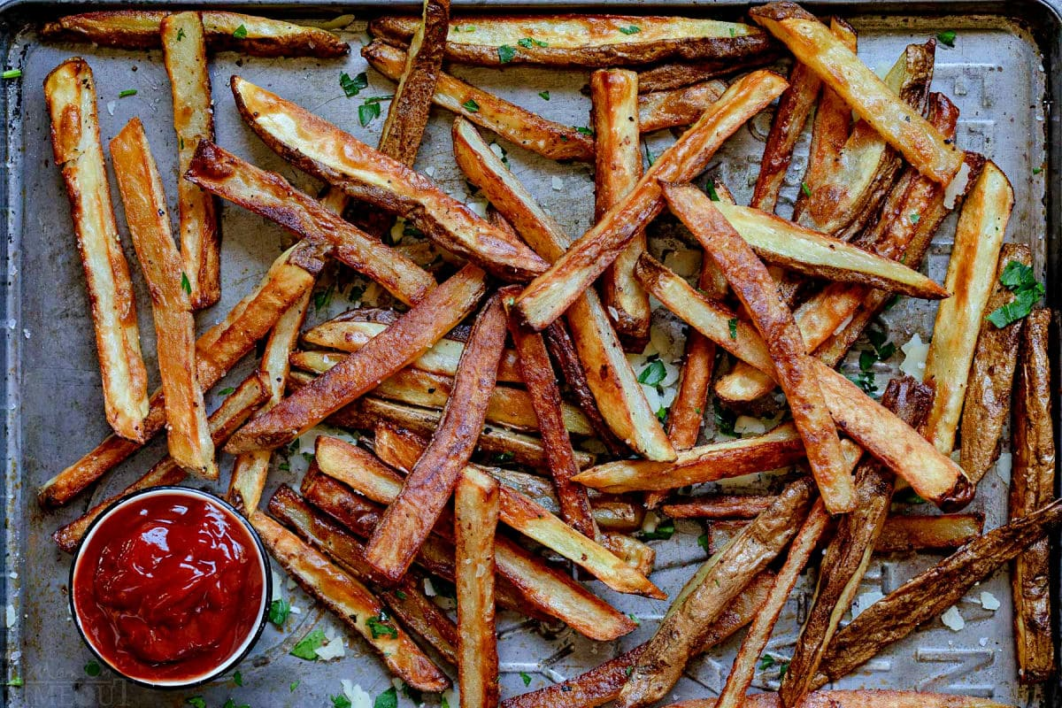 golden fries on baking sheet after being baked in the oven.