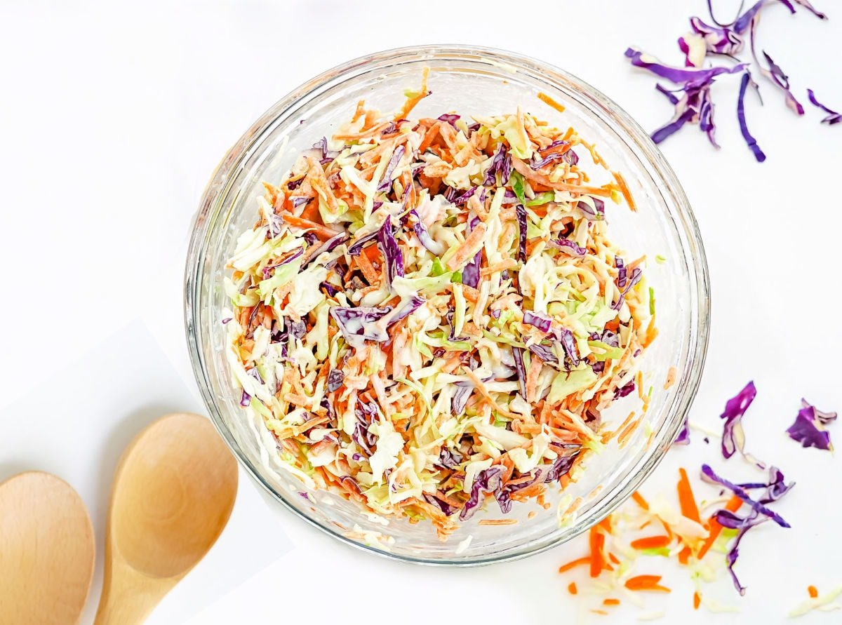 cole slaw recipe tossed together in glass mixing bowl.