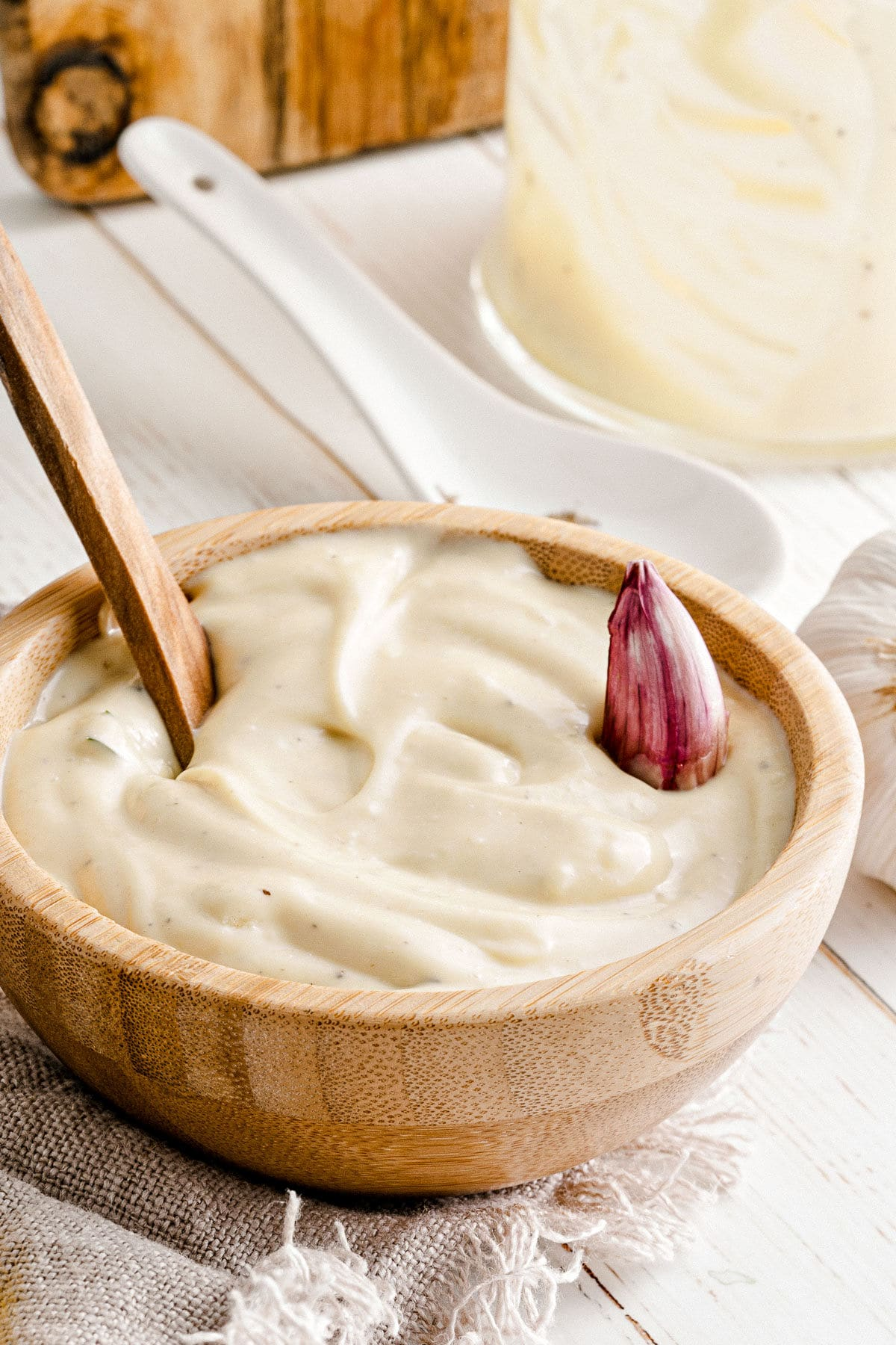 garlic aioli served in wood bowl with spoon inserted and garlic clove resting on top of aioli.