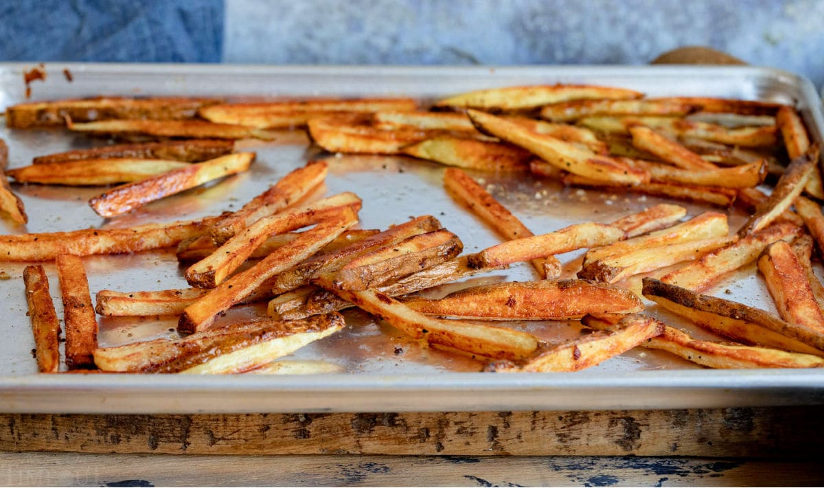 golden and crispy oven baked french fries on large baking sheet.