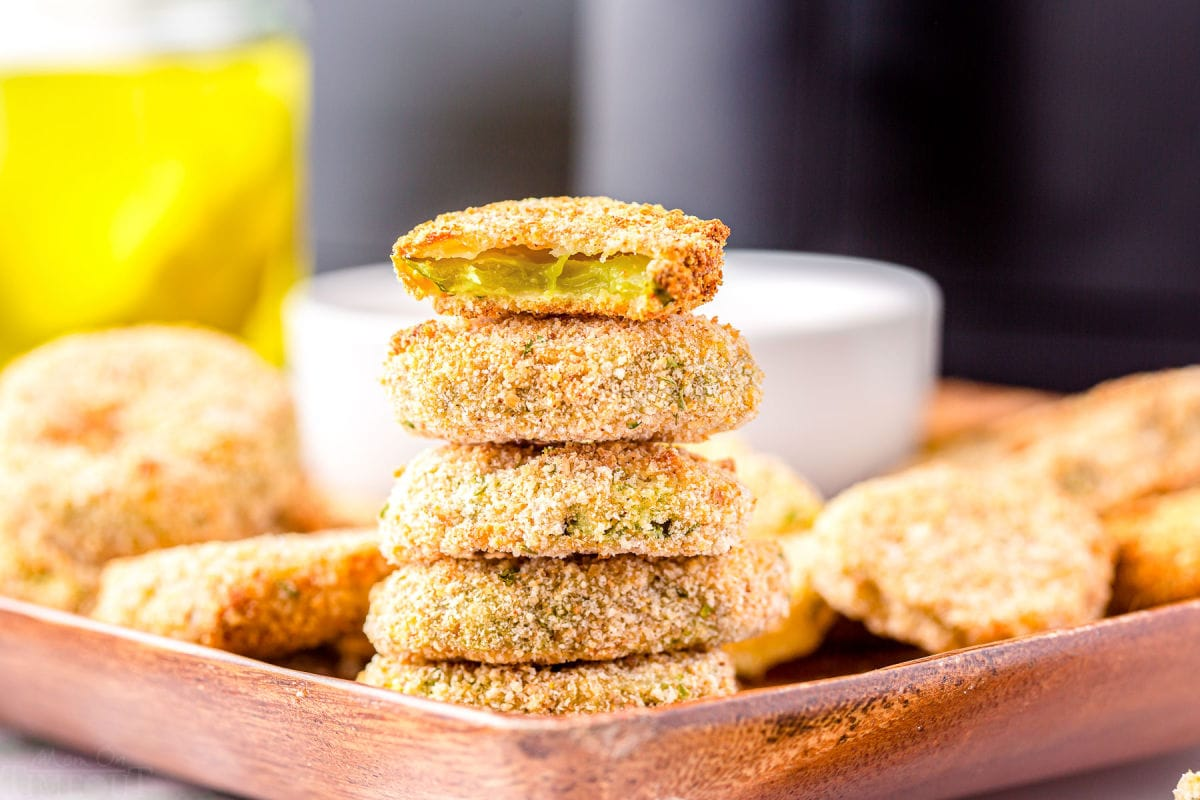 air fryer pickles stacked 5 high with the top pickle bitten in half.