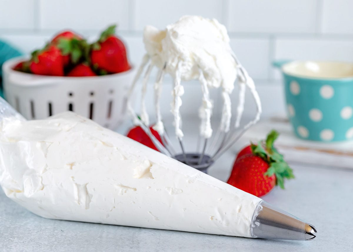 whipped cream in a piping bag and on a whisk attachment.