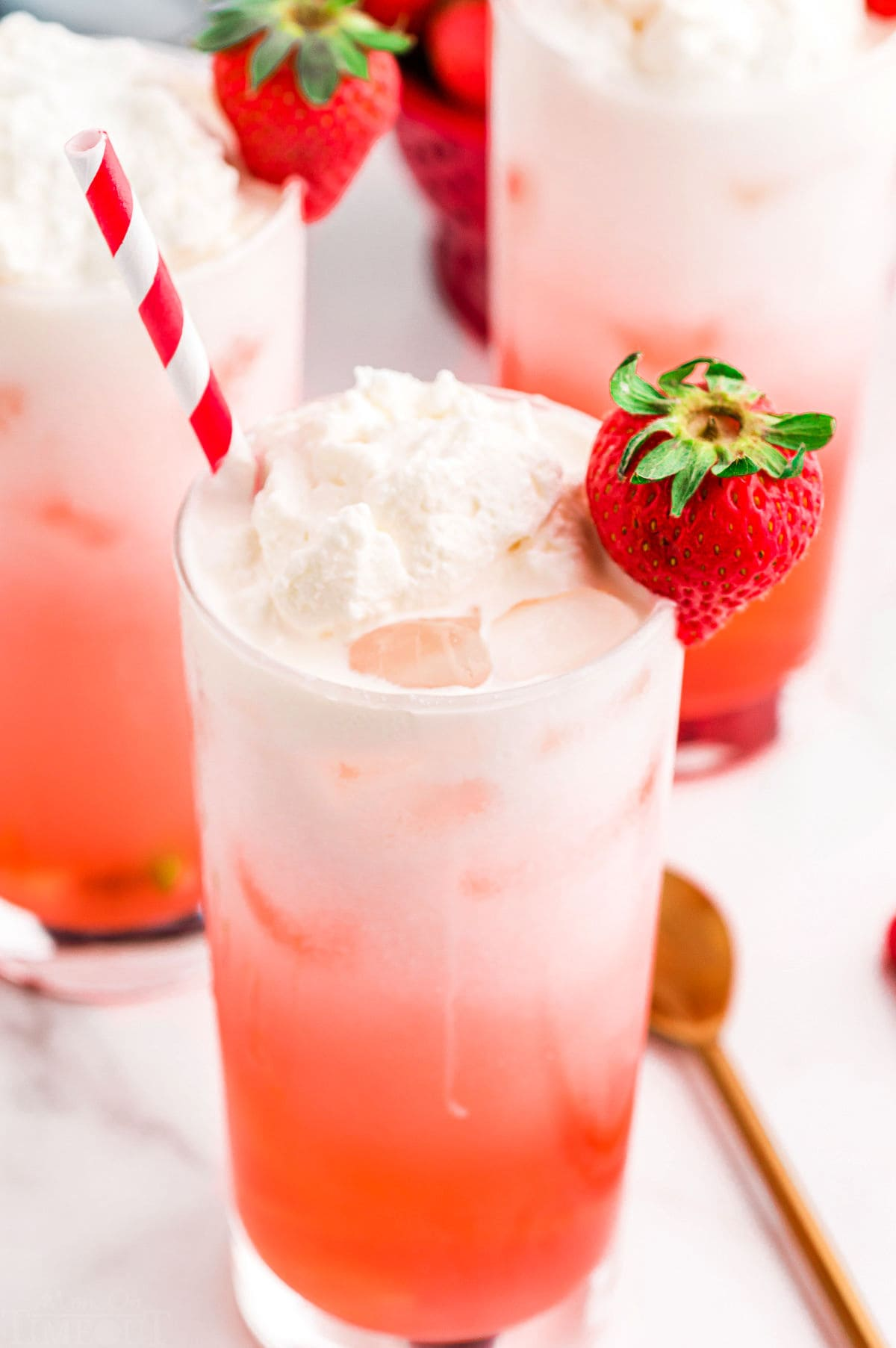 top down look at filled glass with italian soda flavored with strawberry syrup. red and white striped straw in the glass.