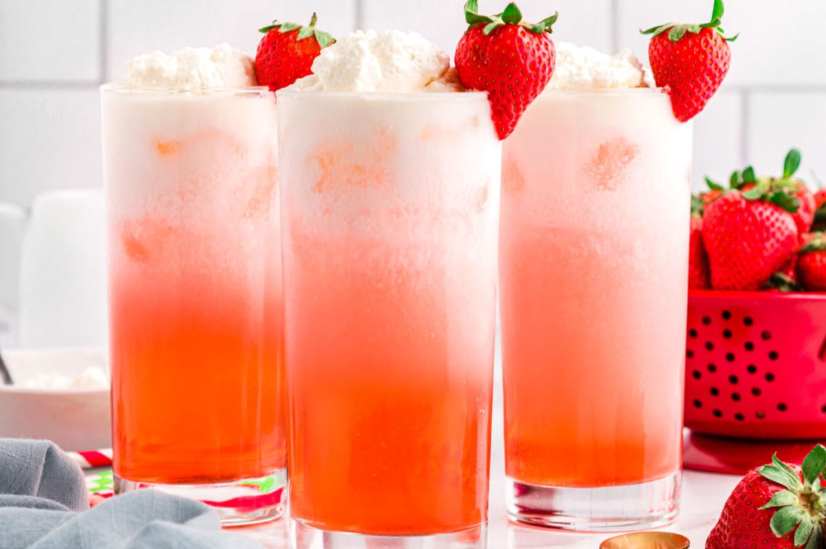 line up of 3 italian sodas garnished with fresh strawberries.