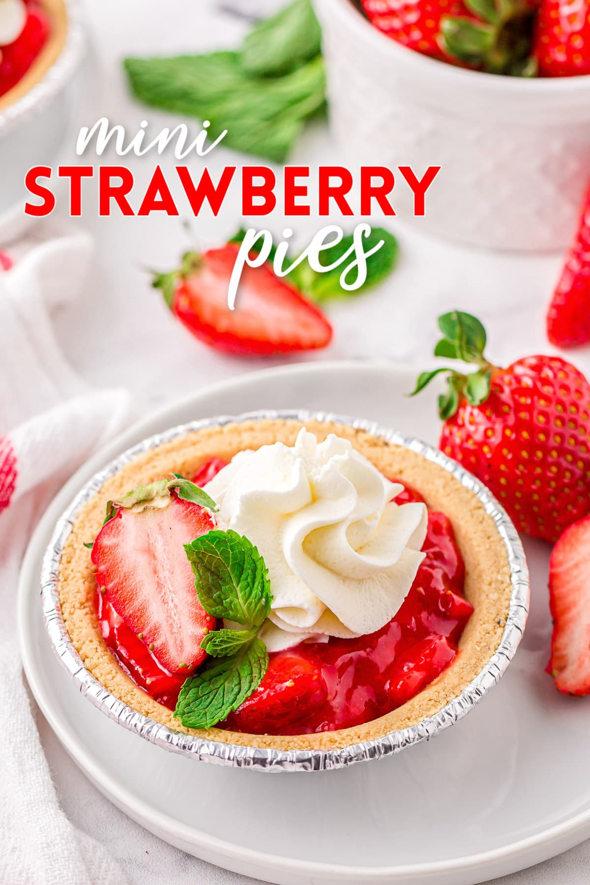 easy fresh strawberry pie recipe made in mini graham cracker crusts topped with whipped cream and a mint leaf. title overlay at top of image.