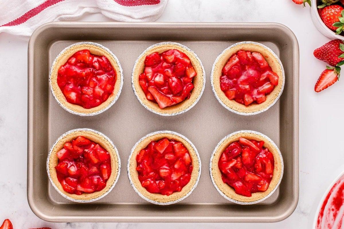 strawberry filling in six mini graham cracker crusts on sheet pan.