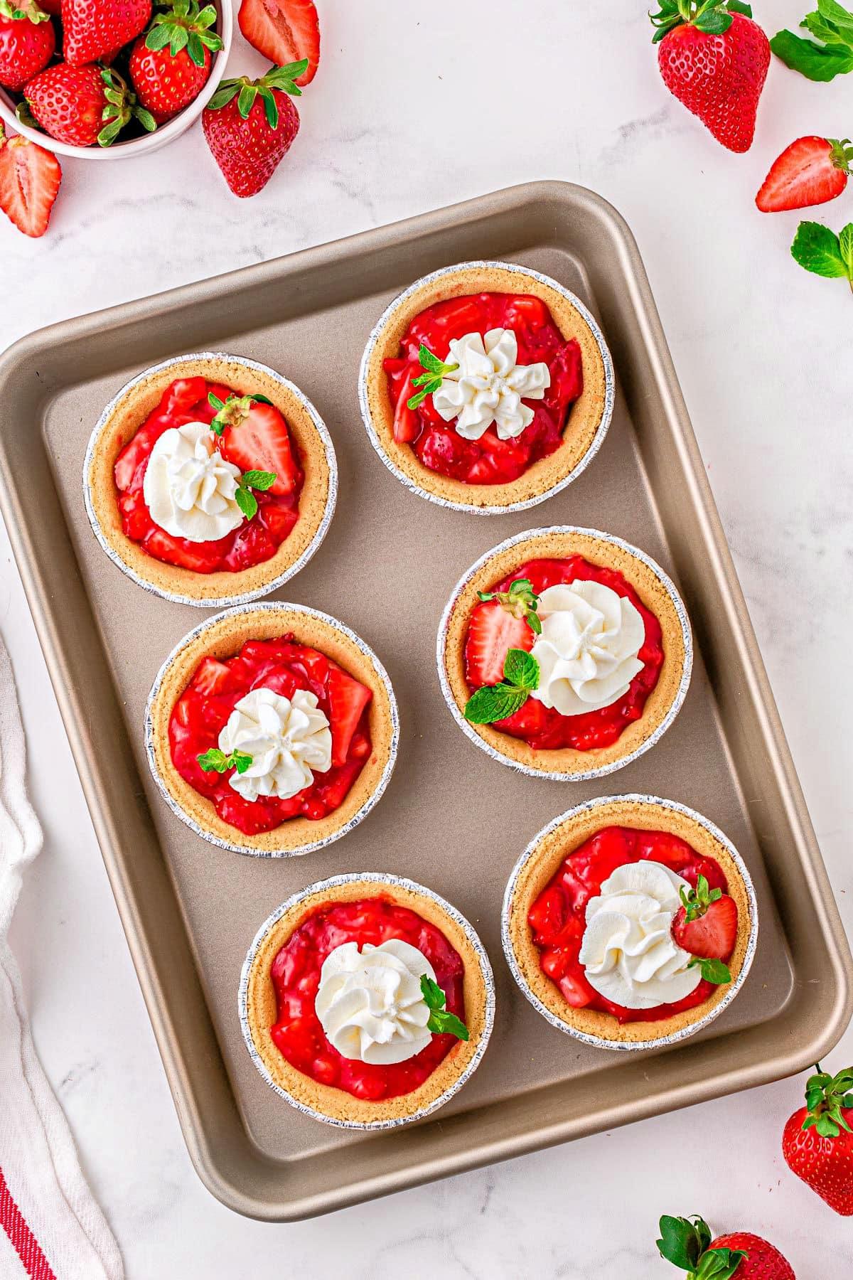 six mini strawberry pies on a baking sheet.