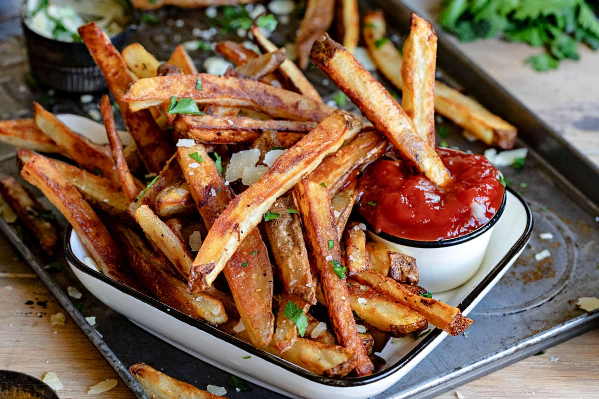 crispy oven fries sitting on white plate with small container of ketchup.